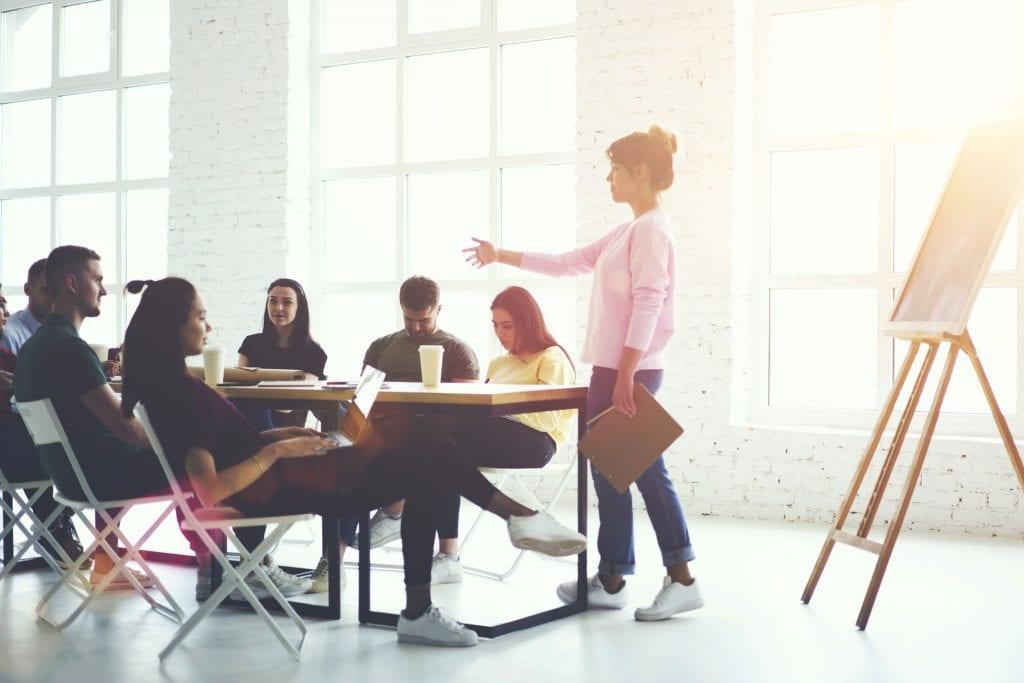 Eine Gruppe sitzt an einem Tisch während einem Change-Management-Seminar