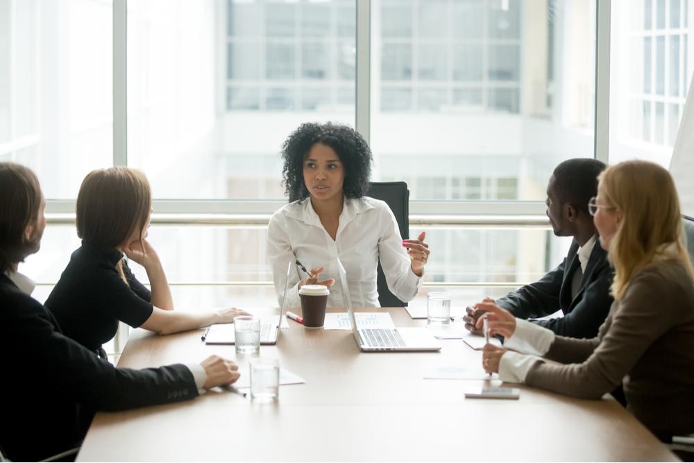 Frau am Tisch im gespräch mit ihren Kollegen während einem Change Management Seminar