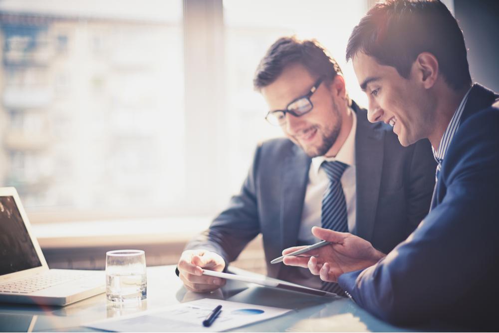 Chef sitzt nach einem Führungskräftetraining an einem Schreibtisch und führt ein Gespräch mit einem Mitarbeiter