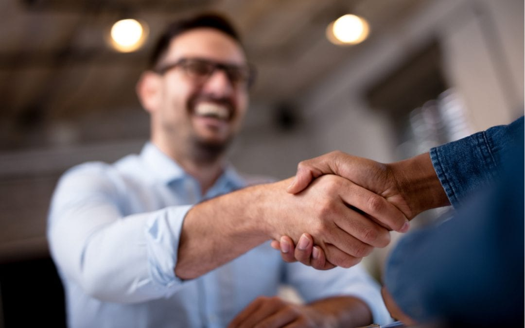 Zwei Männer geben sich die Hände (nonverbale Kommunikation)